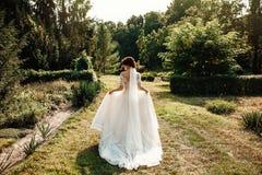 A noiva bonita em um branco levanta no parque Imagens de Stock