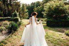 A noiva bonita em um branco levanta no parque Fotografia de Stock Royalty Free