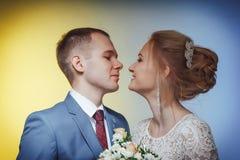 Noiva bonita em um vestido branco e em um noivo novo em um terno azul no estúdio fotografia de stock