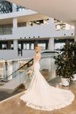 A noiva bonita em um vestido branco está perto da janela no hotel fotos de stock royalty free