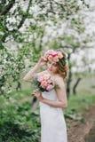 A noiva bonita em um vestido de casamento com ramalhete e as rosas envolvem o levantamento em um jardim verde Imagem de Stock