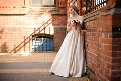 Noiva bonita em uma posição branca do vestido de casamento perto da parede de tijolo vermelho fotos de stock
