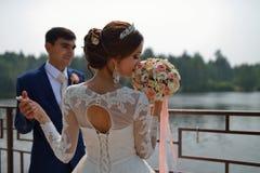 A noiva bonita está cheirando o ramalhete do casamento, noivo à moda que guarda sua mão no fundo imagem de stock royalty free