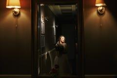 Noiva bonita lindo com o ramalhete que levanta no corredor escuro dentro fotos de stock