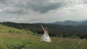 Noiva bonita na estada do vestido de casamento nas montanhas Levanta sua m?o acima video estoque