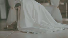 Noiva bonita na roupa interior branca que senta-se na cama em seu quarto e que põe sobre meias video estoque