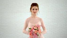 Noiva bonita no vestido cor-de-rosa com o ramalhete colorido de rosas frescas filme