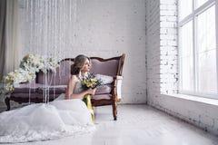A noiva bonita no vestido de casamento branco está sentando-se perto do sofá na frente da janela e está guardando-se o ramalhete foto de stock