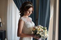 Noiva bonita no vestido de casamento com o ramalhete das flores Foto de Stock