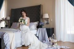 Noiva bonita no vestido de casamento com o ramalhete das flores Imagens de Stock