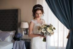 Noiva bonita no vestido de casamento com o ramalhete das flores Fotografia de Stock