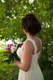 Noiva bonita no vestido de casamento com o ramalhete das peônias Fotografia de Stock Royalty Free