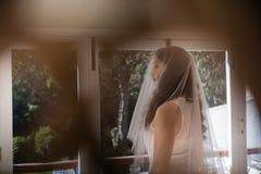 Noiva bonita no vestido de casamento que olha através da janela Imagens de Stock Royalty Free