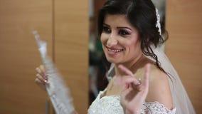 Noiva bonita nova com o fã no vestido de casamento branco video estoque