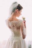 Noiva bonita nova e sonhadora elegante em um vestido de casamento luxuoso do laço que guarda a rosa do rosa foto de stock royalty free