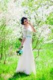 Noiva bonita nova em um jardim de florescência na mola Fotos de Stock