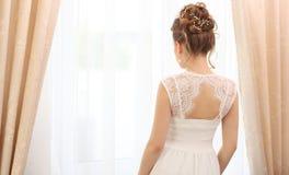 Noiva bonita que está na janela, vista traseira Manhã da noiva Obtenção pronto imagem de stock