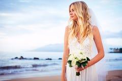 Noiva bonita que está pela praia no por do sol Imagens de Stock