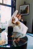 Noiva bonita que senta-se em joelhos de seu noivo bonito em um interior luxuoso com as janelas brilhantes como o backgroundand à  fotografia de stock