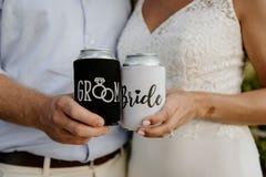 Noiva caucasiano entusiasmado & noivo Posing ao mostrar fora a bebida preto e branco feita sob encomenda Koozies da bebida em seu foto de stock royalty free