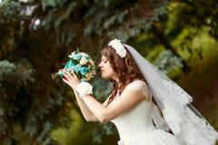 A noiva com cabelo encaracolado e um véu guarda um ramalhete bonito em suas mãos imagens de stock