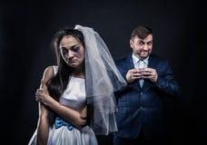 Noiva com cara choroso e noivo com sorriso manhoso fotos de stock royalty free