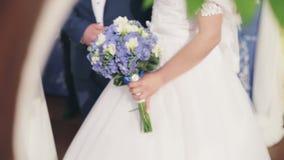 Noiva com o ramalhete de flores e do noivo cor-de-rosa no terno azul junto na cerimônia de casamento video estoque