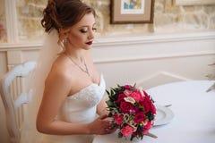 A noiva com ondas e os bordos vermelhos senta-se em um salão brilhante e admira-se seu ramalhete brilhante de rosas vermelhas e c fotografia de stock royalty free