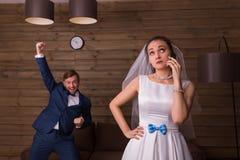 Noiva com telefone celular contra o noivo feliz imagens de stock