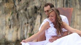 A noiva corrige o véu do vestido de casamento que senta-se na frente do noivo no barco filme