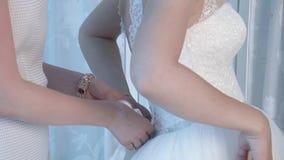 A noiva da noiva ajuda a noiva a vestir um vestido de casamento, close-up vídeos de arquivo
