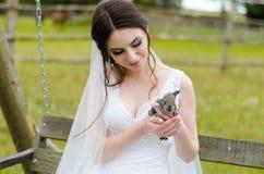Noiva da jovem mulher que sorri e que mantém o coelho bonito sobre a natureza do verão do parque exterior Vestido de casamento br Imagens de Stock Royalty Free