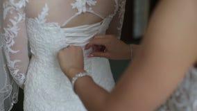 Noiva da manhã Dama de honra que ajuda a noiva que ata acima de seu vestido As amigas ajudam a noiva a prender um vestido video estoque