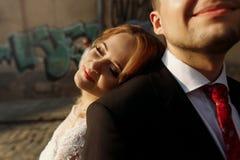 Noiva de sorriso bonita no vestido de casamento branco do vintage que inclina a fotografia de stock