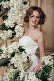 Noiva de sorriso cercada pelas flores brancas Fotos de Stock