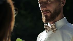 Noiva de sorriso que fixa o bowtie na camisa do ` s do noivo Momentos felizes no movimento lento vídeos de arquivo
