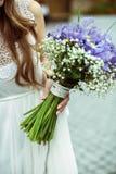 A noiva delicada guarda um ramalhete do casamento dos açafrões violetas nela Imagem de Stock