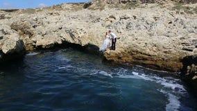 A noiva do noivo salta fora de um penhasco no oceano vídeos de arquivo
