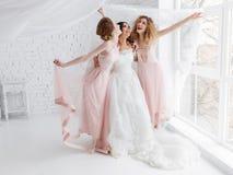 A noiva e as damas de honra de riso jogam na sala branca do estúdio que está sob o véu foto de stock