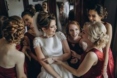 Noiva e damas de honra bonitas ao lado da janela grande imagem de stock royalty free