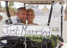 Noiva e noivo em um carro de golfe Imagens de Stock Royalty Free