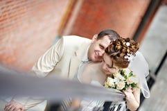 Noiva e noivo felizes em escadas no parque Fotografia de Stock