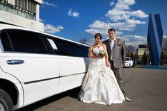 Noiva e noivo felizes perto do limo do casamento fotos de stock