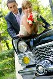 Noiva e noivo que estão o carro próximo do casamento imagem de stock royalty free