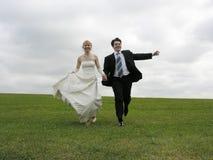 Noiva e noivo que funcionam no prado Fotos de Stock