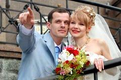 Noiva e noivo que olham em algum lugar e sorriso. Imagem de Stock