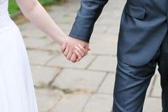 Noiva e noivo que prendem cada outro mãos Fotos de Stock