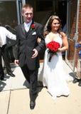 Noiva e noivo que retiram a igreja Fotografia de Stock