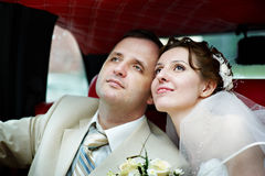 A noiva e o noivo em uma limusina do casamento fotografia de stock