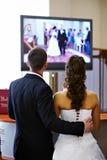 A noiva e o noivo prestam atenção ao vídeo de seu casamento Fotos de Stock Royalty Free